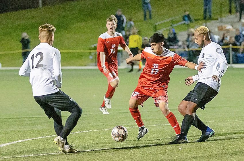 NWC midfielder Jonathan Reynoso works the ball between a pair of Sheridan defenders as teammate Morgan Dowling looks on Friday night at the Region IX tournament in Denver. The Generals won the semifinal contest 4-2, ending the Trappers' season.