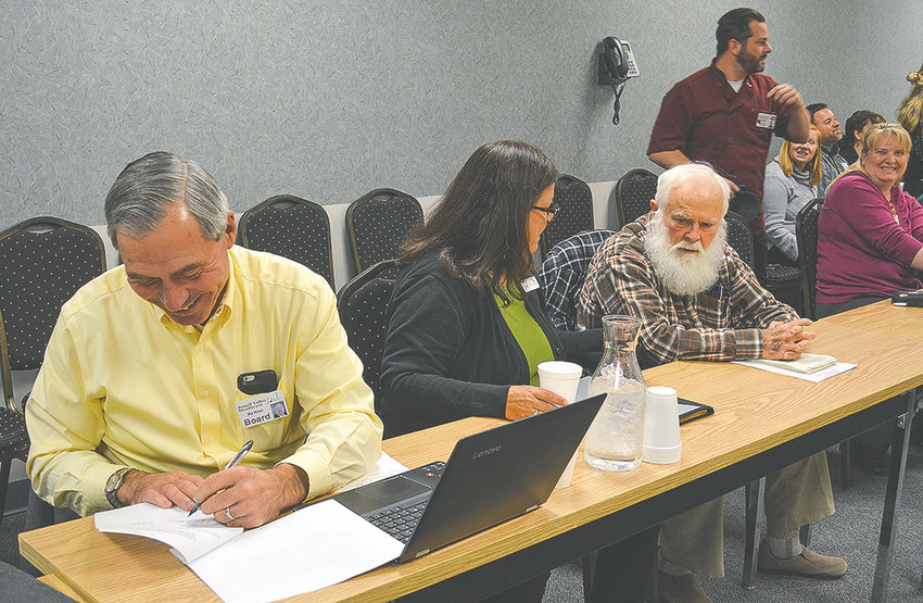 Powell Valley Healthcare Board President R.J. Kost signs a letter of intent to explore an affiliation with Billings Clinic during a Monday meeting at Powell Valley Hospital. Fellow trustees Deb Kleinfeldt and Jim Carlson are pictured to Kost's right.