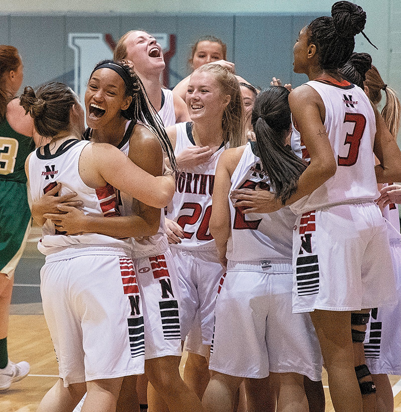 A group of Lady Trappers mob teammate Tayla Sayer (20, center) after Sayer hit the game-winning shot at the buzzer to beat Rocky Mountain JV 69-66 in the team's home opener at Cabre Gym.