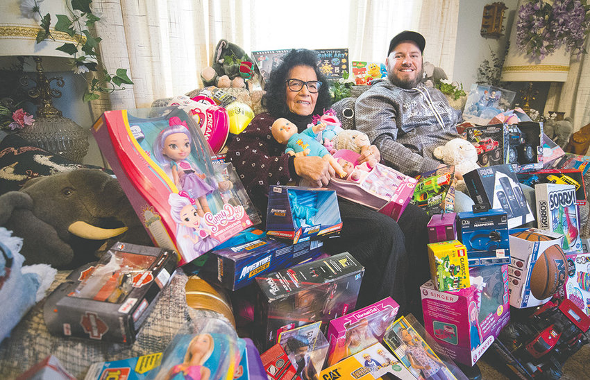 Sally Montoya and Nick Martin, area campaign coordinator for Toys for Tots, sit covered with toys destined to surprise children on Christmas morning. The annual distribution day for Christmas baskets and toys is Friday, Dec. 21.