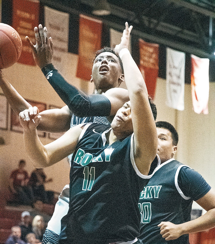 NWC sophomore Calvin Fugett, Jr., goes up and over Rocky Mountain JV's Cleveland Harvey for a bucket during a recent game at Cabre Gym. The Trappers finished 0-2 at last weekend's Lions Club Classic, and will host this weekend's First Bank of Wyoming Shootout beginning Friday.