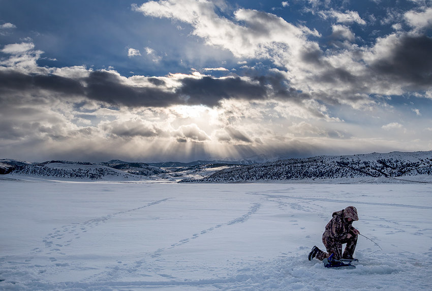 Hunter Burningham, fish culturist with the Wyoming Game and Fish Department, patiently waits for a bite while clouds move on the Lower Sunshine Reservoir Thursday afternoon. He and other Game and Fish hatchery employees used their day off to enjoy the fruits of their labor.