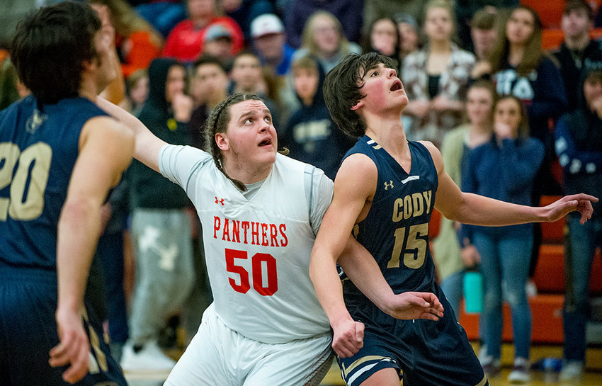 Powell's Kain Baxter battles Cody's Duncan Radakovich for control of the paint during the Panthers' 57-53 win over the Broncs. The win gave PHS the season sweep over their cross-county rivals.