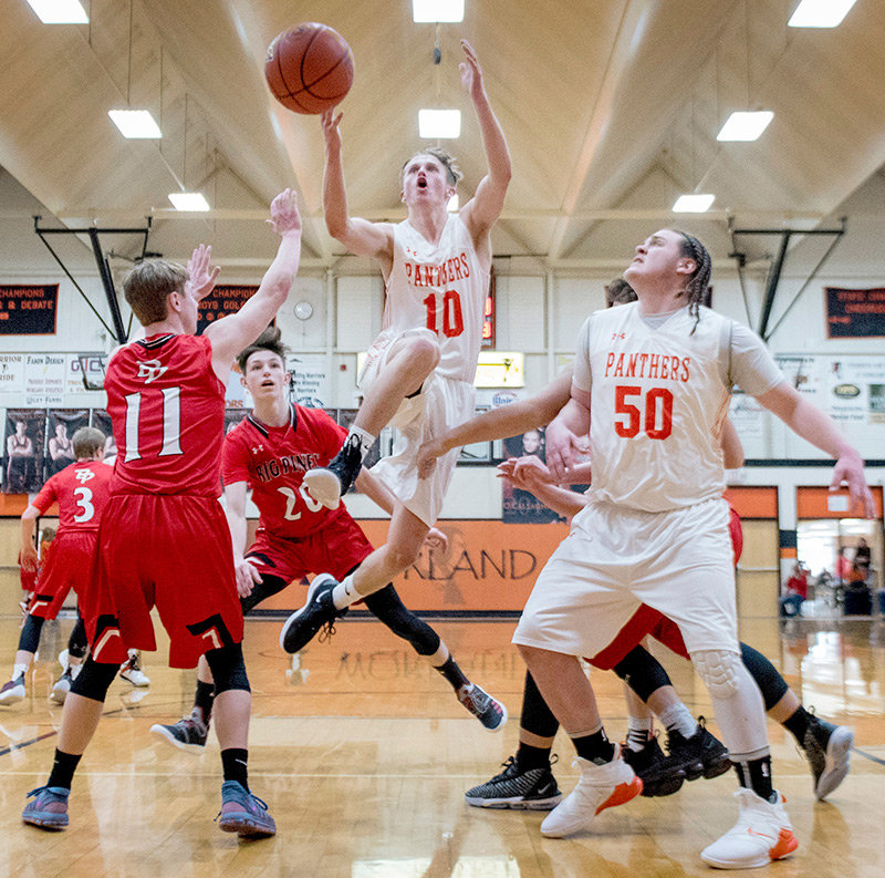 PHS senior Kaelan Groves takes to the air for a shot over Big Piney's Bryan Pluid as teammate Kain Baxter, right, looks on during the Panthers' 61-39 win over the Punchers in the 3A West Regional Tournament on Thursday.
