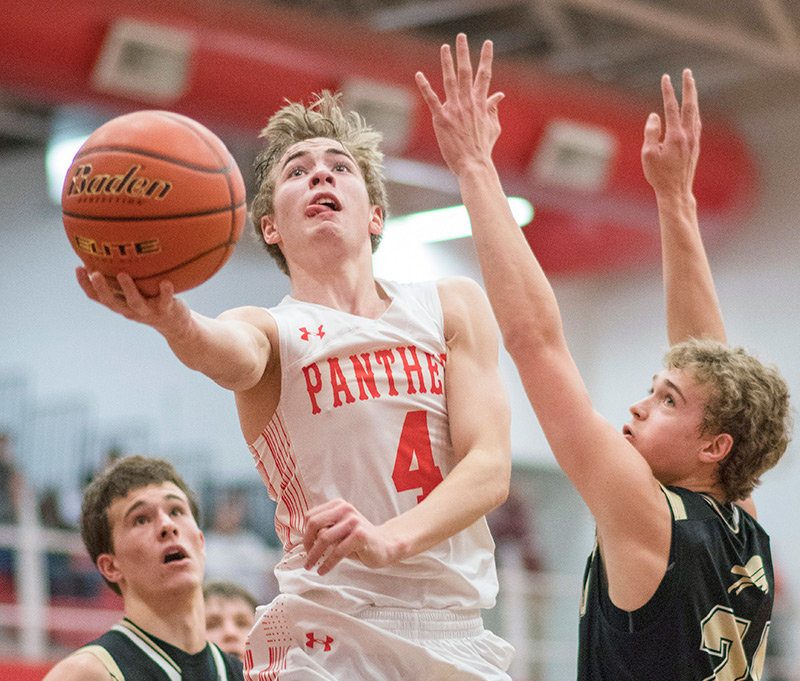 Powell's Mason Marchant scores two of his team-high 20 points over Buffalo's Aaron Thiele (left) and Hunter Stone during the Panthers' 66-64 semifinal round upset of the Bison at Casper College Friday night. Marchant averaged 17 points a game for the 3A State Basketball Tournament.