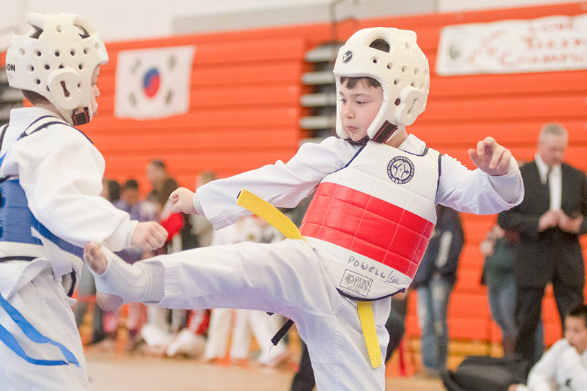 Tug Cadwallader, right, of Lone Wolf Martial Arts in Powell, launches a kick at an opponent during the Lone Wolf Taekwondo Championships, held at Powell High School this month.