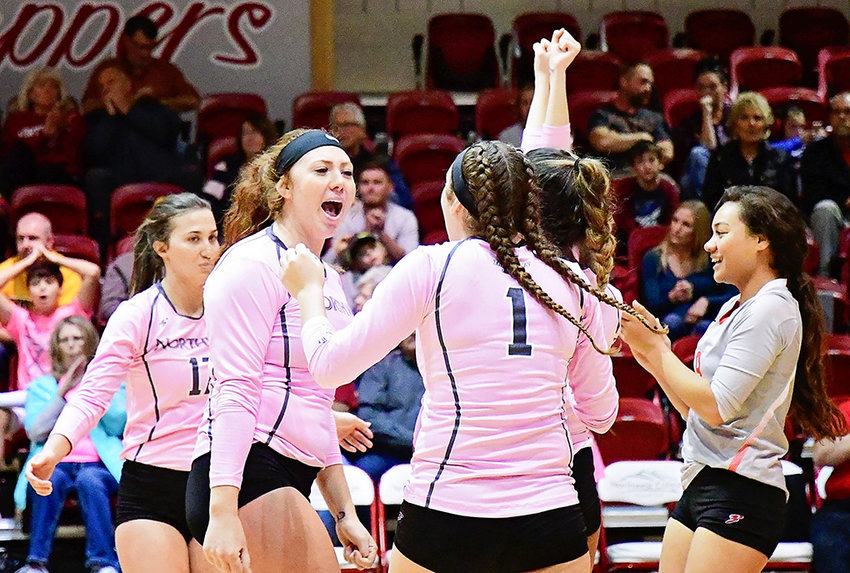 Lady Trapper volleyball player Tammy Maddock, left, celebrates a point with Jess Ruffing (No. 1) and other teammates during a match last season against Eastern Wyoming. Maddock and Ruffing will continue their volleyball careers at four-year schools next season.