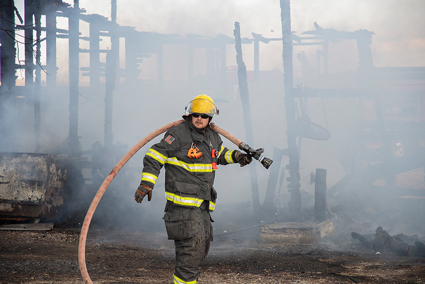 Chris Schuler, a firefighter for the Powell Volunteer Fire Department, fights a structure fire at 646 Lane 7 on Saturday afternoon. Fire crews were kept busy over the weekend, largely due to grass fires growing out of control.