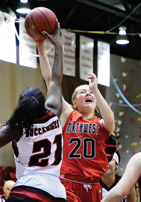 Northwest sophomore Tayla Sayer, right, battles for a shot against Dawson's Alexius Foster during a game at Cabre Gym last season. Sayer recently signed her letter of intent to play basketball at College of Idaho next season, reuniting with former Lady Trappers' coach Janis Beal.