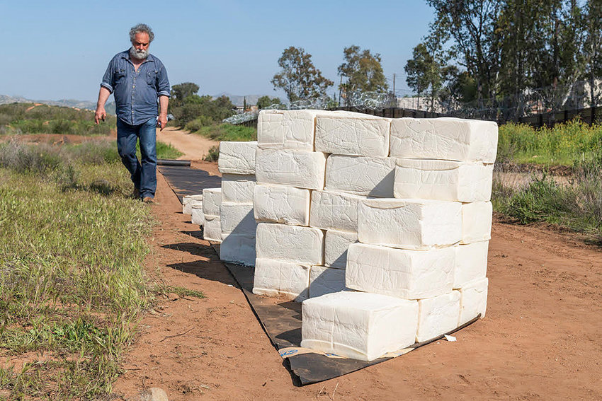 Using blocks of spoiled cheese, Cosimo Cavallaro is building a wall at the U.S.-Mexico border. Cavallaro brought his unusual artwork to Powell in 2001, when he covered a small cottage with cheese.