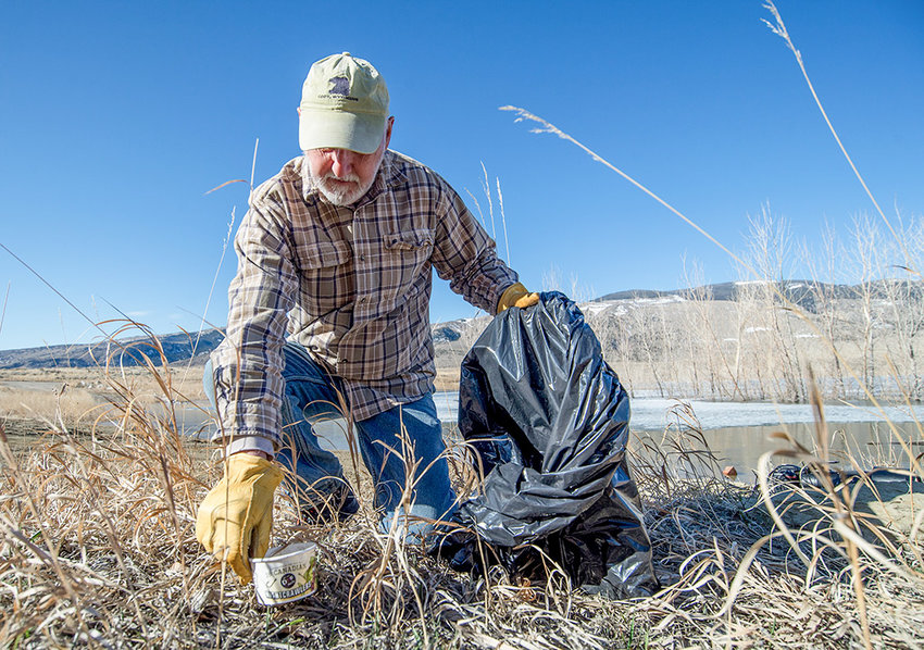 Mark Vondersaar, a part-time adjunct professor at NWC, picks up debris along the shore at West Newton Lake outside of Cody as part of a Sunday cleanup effort.