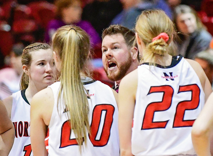 NWC head women's basketball coach Camden Levett discusses strategy with Lady Trappers Shelby Wardell, left, Tayla Sayer and Tess Henry during a game last season. Levett was hired last week as the team's permanent coach.