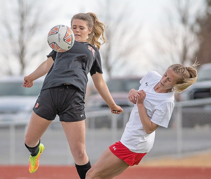 Lady Panther Kortny Feller wins a ball over a Riverton opponent on Monday at Panther Stadium. Powell held a 1-0 lead at halftime of the 3A West contest, but Riverton stormed back in the second half to win 2-1.