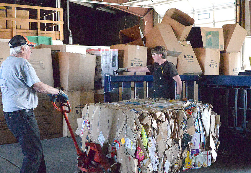 Jerry Barton pulls a 1,300-pound block of cardboard out of a baler Friday, while Dustin Curtis holds the door open at the Powell Valley Recycling Center. Once a valuable commodity, cardboard has lost more than half its value in the past year.