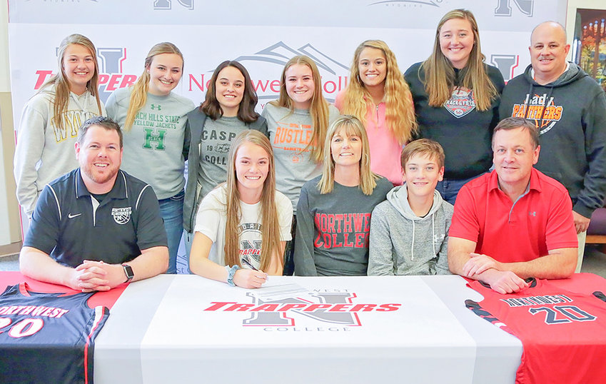 PHS senior Aubrie Stenerson (front row, second from left) is all smiles as she signs her letter of intent to play basketball next season for Northwest College. Cheering her on are Lady Panther teammates Maddie Fields, Katie McKenzie, Karlie McKenzie, Ashtyn Heny, Brea Terry, Rachel Bonander and head coach Scott McKenzie. In the front row are NWC head coach Camden Levett and Aubrie's family: mom Christy, brother Trey and dad Colby.