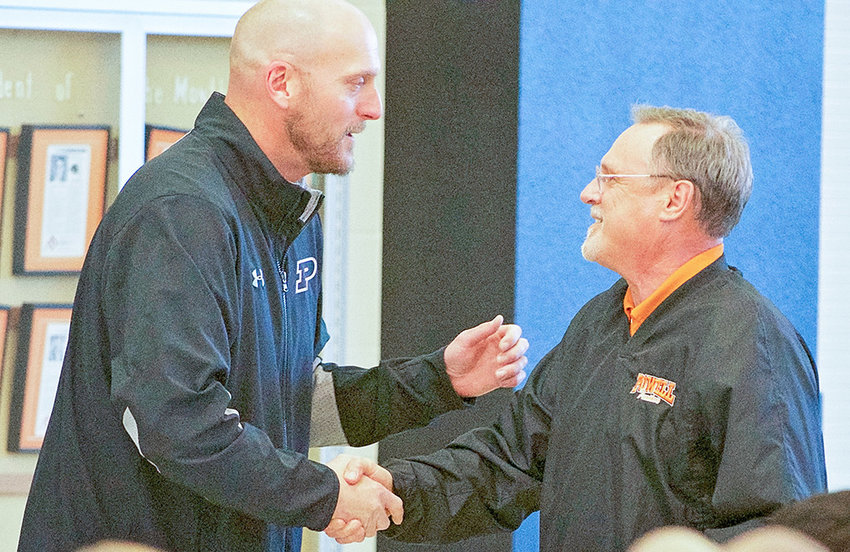 PHS activities director Tim Wormald (left) shakes the hand of PHS principal Jim Kuhn Monday evening at the 2019 Athletic Awards ceremony. Kuhn was given special recognition as he prepares to step down as principal; Wormald has been tapped to replace him.