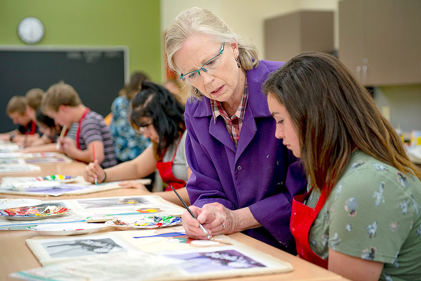 Powell Middle School art teacher Jane Woods helps Lilly Morrison with a painting during class last week. Alexis Homewood also is pictured in the background. Woods was recently named Powell's Teacher of the Year.