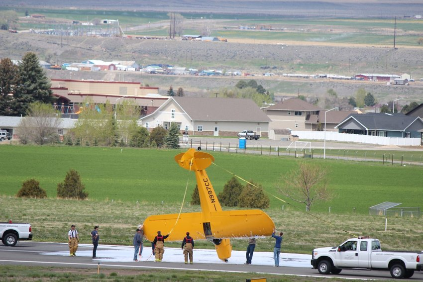 Firefighting personnel and others work to right a plane that flipped over while landing at Yellowstone Regional Airport on Saturday morning. A student pilot and flight instructor on board were not injured.
