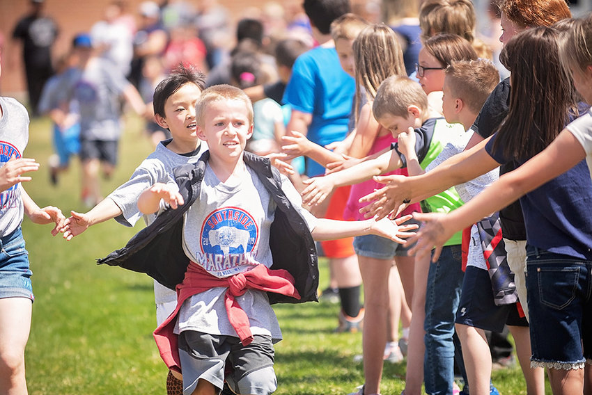 Southside runners Tanner Myrick and Kevin Zhang receive a congratulatory line of 'high fives' as they make their way around the playground for the final lap of the marathon. A total of 194 students qualified for the marathon in the 2018-19 school year.