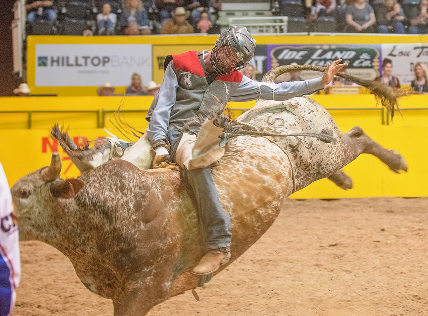 Aboard a bull named Game Changer, Northwest College's Caleb McMillan rides to a 78.5 point score during day one of the College National Finals Rodeo in Casper.