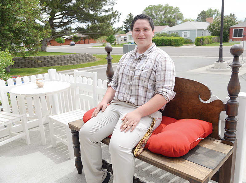 Isaac Gutierrez sits on a bench outside The Heartland. Gutierrez brought in a headboard he thought one of the residents might like to use on their bed. His friends, Andy Beavers and Mark Pappenfort, used their woodworking skills to turn it into a bench.