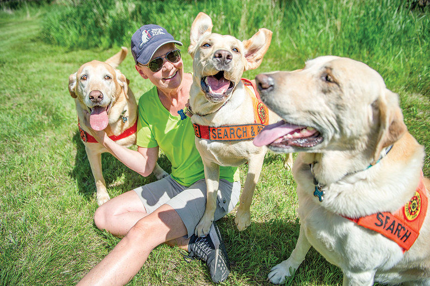 From left, Mitch, Colt and Charlie surround Kris Brock, a longtime member of Park County Search and Rescue, before training at Beck Lake in Cody. The dogs are highly trained in finding humans, dead or alive.