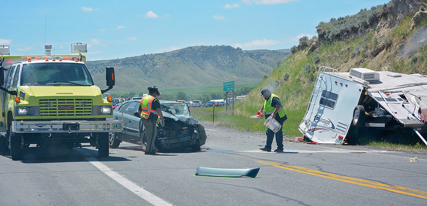 Investigators examine the scene of a fatal accident on June 29 at the intersection of WYO 120 and County Road 3LE.