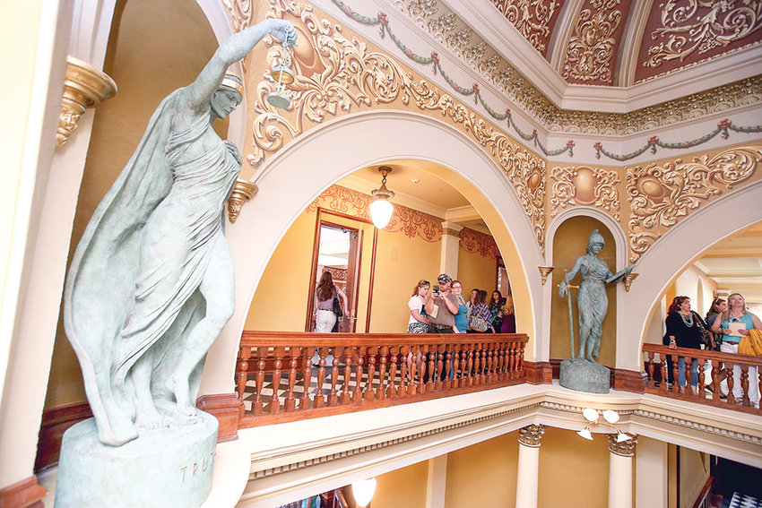 Visitors look at new statues — allegorical sculptures representing hope, courage, justice and truth — while touring the renovated Capitol in Cheyenne during a Wednesday grand reopening. Restoration of the 130-year-old Capitol took four years and cost more than $300 million. It was reopened with fanfare to the public on Statehood Day.