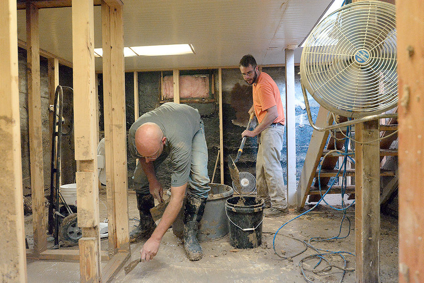 Homeowner Jared Fink (right) and his cousin Jason Fink (left) work to clean up the basement of his South Gilbert Street home on Wednesday afternoon. Like many other residents who didn't have flood insurance, Jared Fink and his fiance Donna Frassetti may be on their own for cleanup costs from Sunday's storm.
