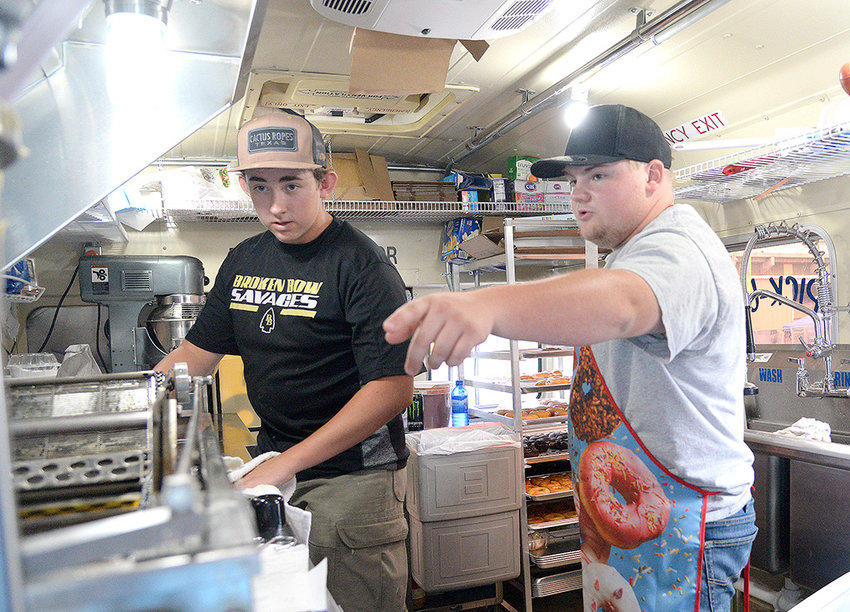 Teenage entrepreneur Andy Beavers (right) makes donuts with his cousin Steven Beavers (left) at the Park County Fair on Tuesday, July 23. Andy Beavers operates out of a van that his father, Brian, converted into a food truck.