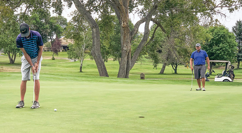 Chris Manning rolls in an eagle on the par-5 16th hole on his way to defending his club championship during the Powell Golf Club Championship on Sunday. Former PGC champion West Hernandez (at right) witnesses the rare bird.