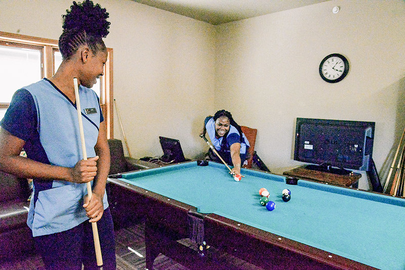 Anmarie Holness watches as Satara Elliott takes a shot in a game of pool at the staff dormitories of the Best Western Sunset Inn in Cody. The facility was built for visa workers, which the company relies upon to fill its seasonal staff needs. Holness and Elliott both hail from Jamaica.