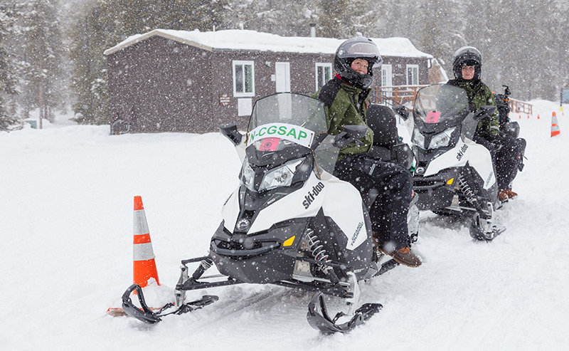 A non-commercially guided group of snowmobilers parks at the Madison Warming Hut in Yellowstone National Park in March 2018. Those wanting to snowmobile through the park without a paid guide this winter can apply to do so, starting today (Thursday).
