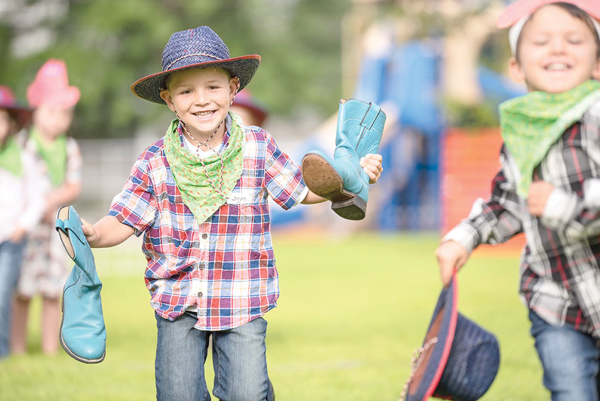 Incoming kindergarten students got an early introduction to school during Jump Start activities last week, which finished with a Friday morning rodeo at Parkside Elementary School. Blake Del Biaggio smiles and holds a pair of teal cowboy boots while Moose Dawe runs with a cowboy hat.