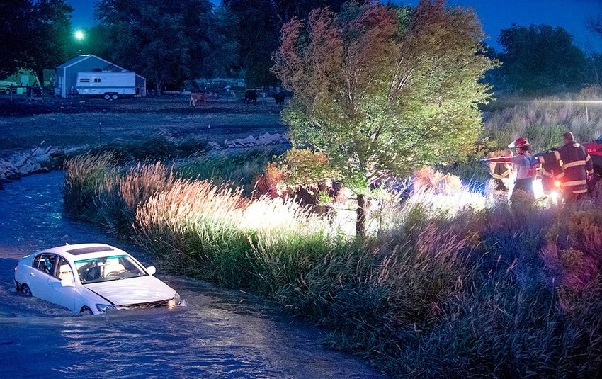 Members of the Powell Volunteer Fire Department spotlight a 2007 Lexus that crashed into Bitter Creek in the Garland area on Thursday night. The driver — who was not injured — reportedly lost control on a recently chip sealed road.