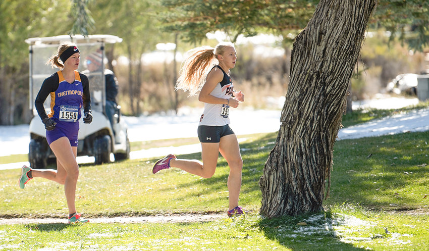 PHS cross country runner Kayla Kolpitcke pulls past Thermopolis' McKenna Bomengen during the Pinnacle Bank Invitational earlier this month at the Powell Golf Club. Kolpitcke finished seventh overall last weekend at the 3A West Conference Meet in Lander, earning All-Conference honors.