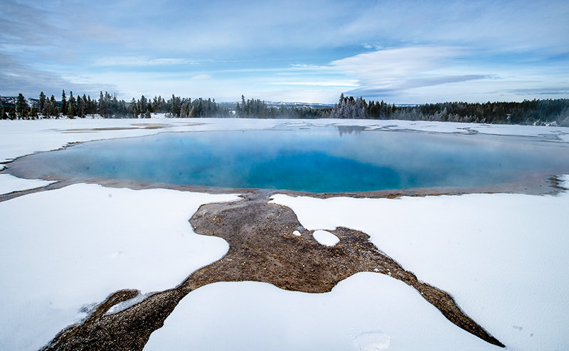 The colors of Turquiose Pool, in the Midway Geyser Basin at Yellowstone National Park, contrast with a layer of fluffy snow Saturday. The Hayden Expedition of 1878 named the pool for its 'milky, white bottom and gem-like, blue-colored water,' according to the park website.