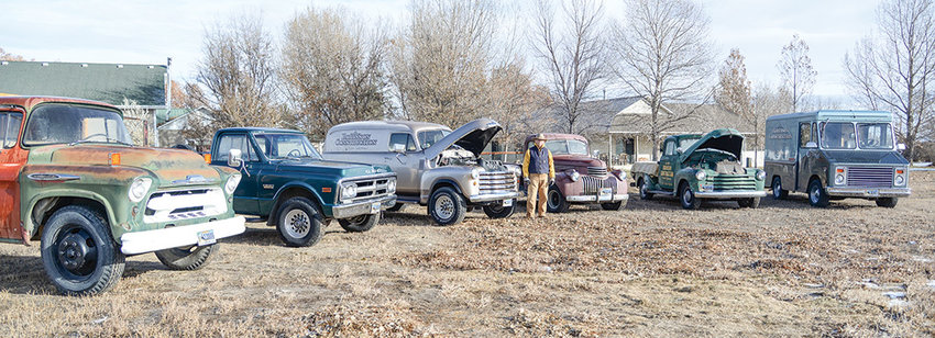 Earl Robinson stands with his fleet of classic vehicles. He uses all the vehicles for his business, Robinson Construction. He enjoys that they stir up memories and conversation with folks around town.
