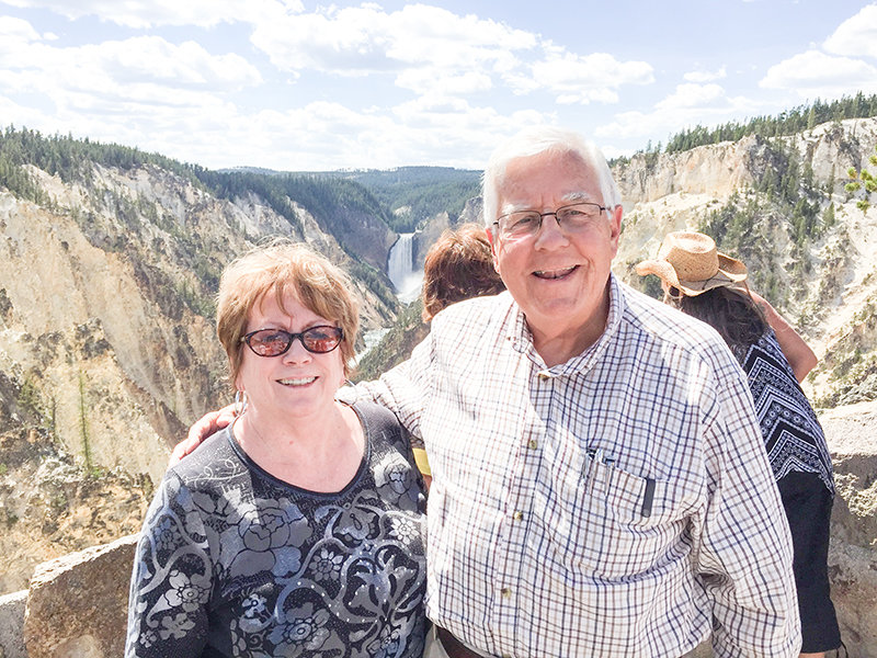 Mike and Diana Enzi pose for a portrait in front of Lower Falls during a recent trip to Yellowstone National Park. Enzi has proposed a bill to help pay for a huge backlog of deferred maintenance in the National Park System, arguing that a different proposal supported by the Trump administration and others doesn't have real money attached to it.