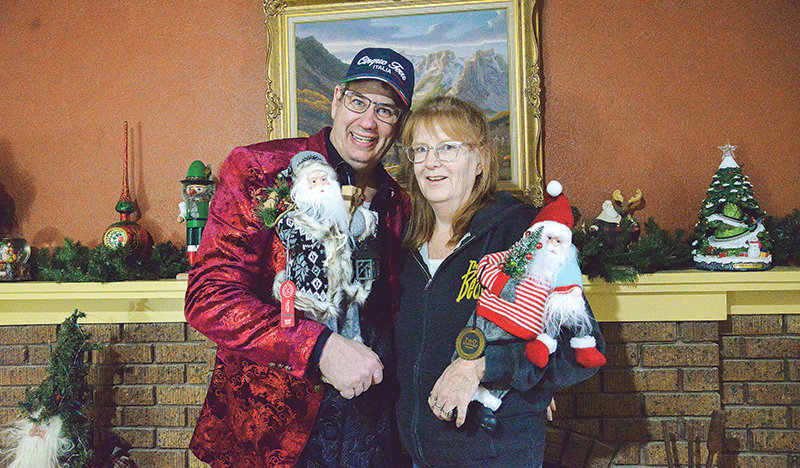 Chris Pelletier and his wife Anita take a break from all the work getting the Kringle House ready for opening to pose in front of the mantle.