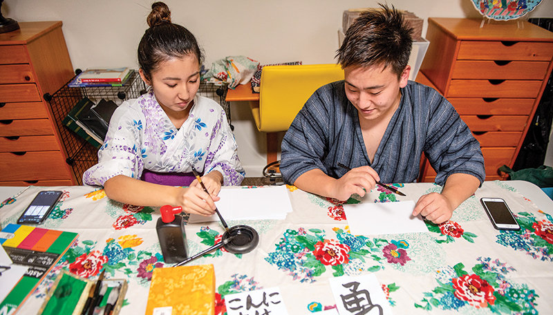 Yuki Abe and Manami Sugiyama, international students at Northwest College in Powell, demonstrate Japanese calligraphy techniques during a celebration of the country's culture at the Intercultural House Nov. 22.