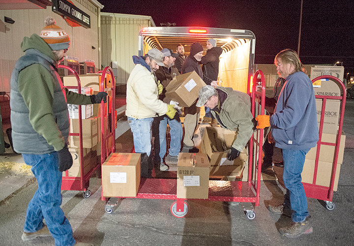 A group of City of Powell employees, including Bill Gullion (at right), help load 112 Christmas baskets before sunrise Monday. The number of families applying for assistance in the annual program has declined in the past two years, down from a high of 144 in 2017.