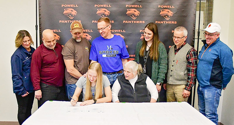 PHS senior Kayla Kolpitcke, with her mother, Linda, at her side, signs to play ice hockey and soccer at Marian University. Backing up the student-athlete they encouraged and nurtured are: (from left) coaches Angie Johnson, Pat D'Alessandro and Josh Westerhold, her father Scott Kolpitcke, and coaches Kaitlin Loeffen, Tom Keegan and Kane Morris.