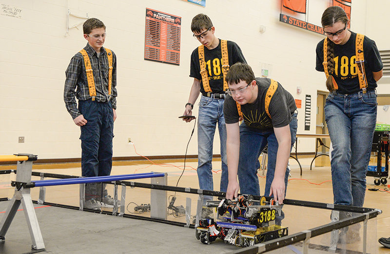 Owen Fink, Daniel Merritt, Cade Sherman, and Jenna Merritt, members of team Squiggle Splat Bang, try out a robot on a test field prior to the competition at the Robo Rumble on Jan. 11.