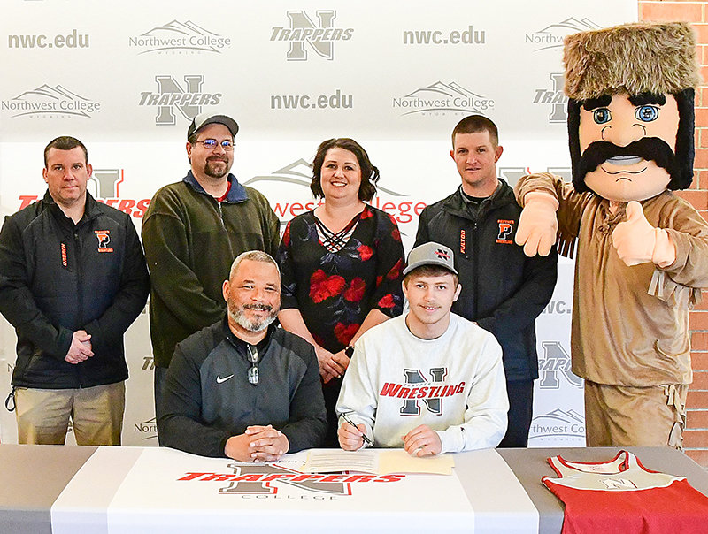 On Tuesday, Powell Panther standout wrestler Bo Dearcorn signs to join coach Jim Zeigler and the Northwest College team next season. There to support Dearcorn are (standing from left): Powell High School head wrestling coach Nate Urbach, parents Casey and Brandy Dearcorn, Panther assistant coach Nick Fulton and the Trapper mascot.