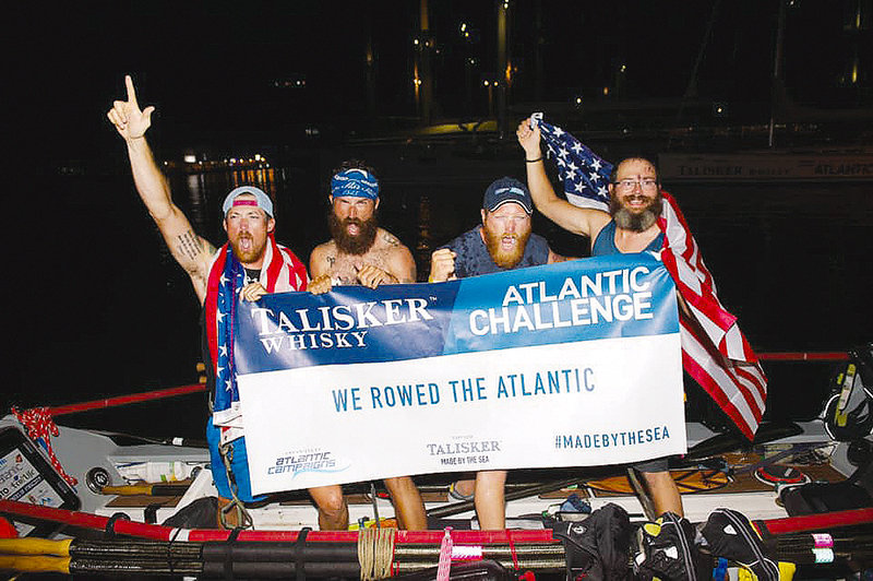 Powell's Carl Christensen (far right), skipper of the Woobie for team Fight Oar Die, celebrates with his crew of John Fannin of Universal City, Texas, Evan Stratton of Denver and Luke Holton of Auke Bay, Alaska, after setting a world record for their boat class in the Talisker Whisky Atlantic Challenge.
