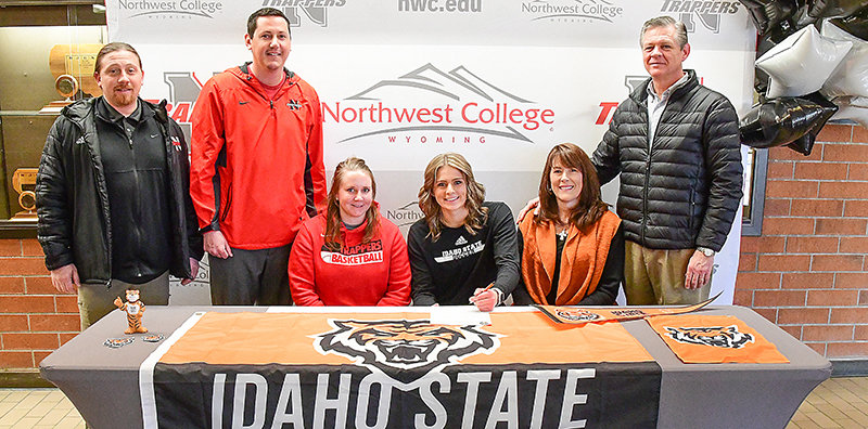 Flanking Trapper soccer player Genevieve Sauers as she signs her full-ride scholarship offer to Idaho State University last week are assistant NWC coach Jamie Krediet (left) and her mother, Joel Sauers; standing (from left) are NWC women's head coach Aaron Miller, NWC athletic director Brian Erickson and her father, Bruce Sauers.