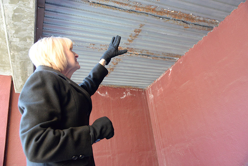 Outside the entrance to the DeWitt Student Center dining hall, Northwest College President Stefani Hicswa points out rust on an iron ceiling. The water rusting the ceiling is coming from a concrete sidewalk above.