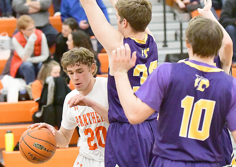 Panther Jesse Brown challenges the baseline defense of Bobcats Chase Moeller and Duder Harvey (10) Friday night in Powell. The Panthers won the home game, 57-50.