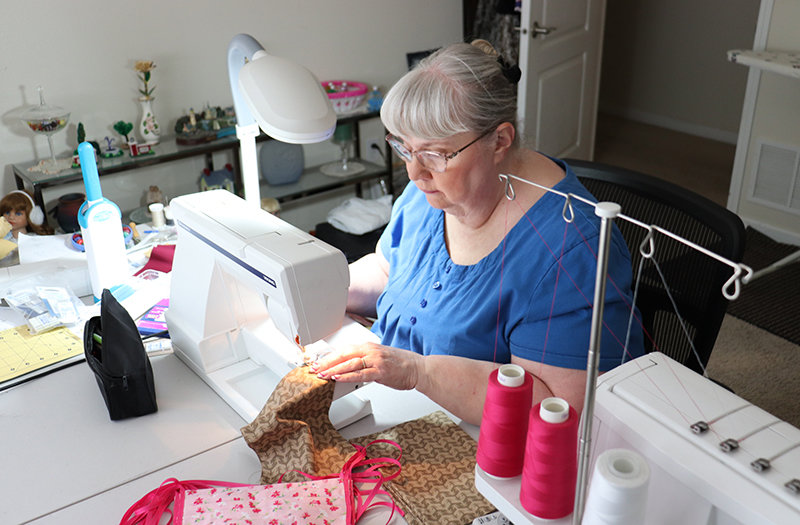 Seamstress Ginger Morrow works to sew a surgical mask from some fabric at her Powell home Tuesday morning. She's one of many local seamstresses who are helping craft personal protective equipment for healthcare providers.